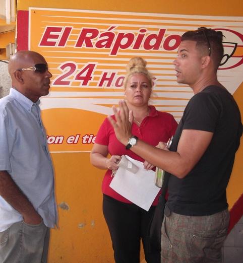 Manuel Vázquez, coordinador del servicio de asesoría jurídica del CENESEX (a la derecha), junto al bloguero Alberto Abreu, intercambia con una de las trajadoras del Rápido donde se desarrollaron los hechos